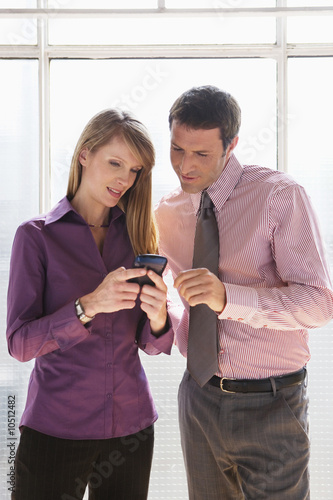 Business man and woman looking at mobile phone