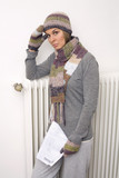 Woman holding utility bill, wearing scarf and cap