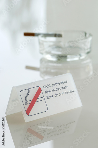 Cigarette in ash tray by non-smoking sign