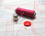 The coil red thread a thimble and a needle on a pattern poster