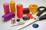 thread coils, measuring tape, thimble, scissors and a needle poster