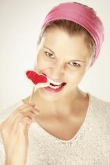Junge Frau isst herzförmigen Lutscher