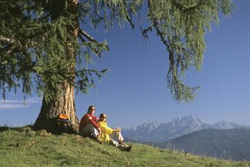 Paar macht Pause unter einem Baum in den Bergen