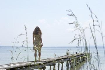 Junge Frau läuft über einen Steg