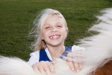 Mädchen mit Pony auf der Wiese, close-up, Portrait,