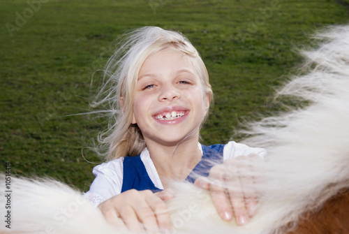 Girl (7-9) with pony on meadow, close-up, portrait, elevated view