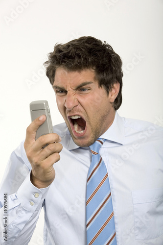 Young businessman holding mobile phone, shouting, close-up