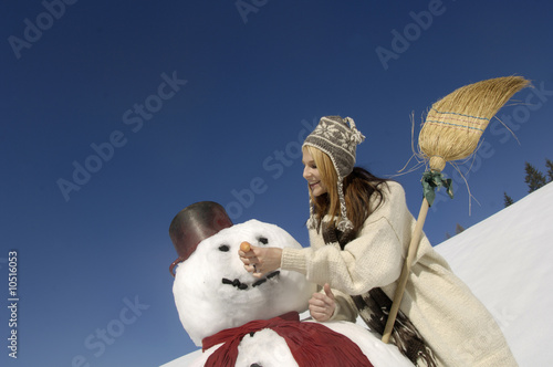 Young woman making snowman, smiling, low angle view