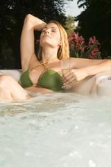 Frau entspannt in der Badewanne, mit Getränken