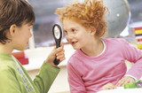 Boy and girl (7-9) fooling around with magnifying glass