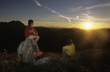 Paar bei Sonnenuntergang in den Bergen