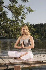 Frau bei Yogaübungen auf einem Steg