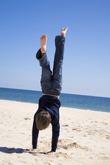Portugal, Algarve, Jungen machen Handstand am Strand, Rückansicht