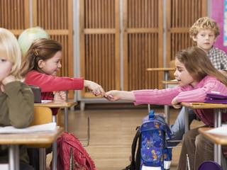 Mädchen austauschen von Notizen im Klassenzimmer