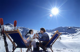 Couple sitting on deckchair in snow toasting glasses, side view