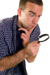 A young man with a magnifying glass searching for something