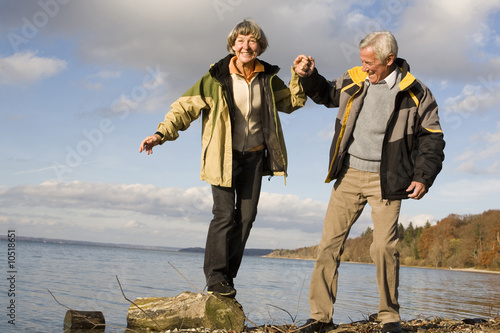Senior couple by sea, woman standing on wood, smiling