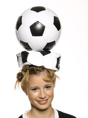 Mädchen balanciert Fußball auf dem Kopf