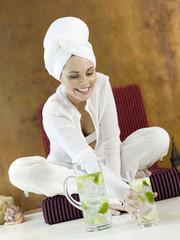 Frau sitzen auf Kissen halten Glas Limetten Wasser, lächeln