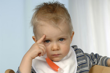Kleiner Junge beim Essen, Finger an der Stirn, du bist doof