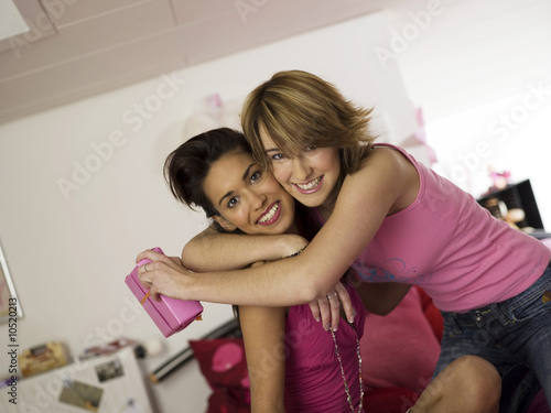 Two teenage girls (16-17), holding gift