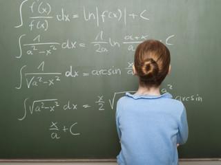 Mädchen stehen vor der Tafel, Rechenaufgabe lösen, Rückansicht