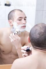 Mann im Badezimmer, mit Rasierschaum im Gesicht