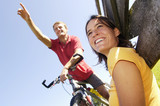 Man sitting on bicycle, woman leaning on wooden railing, smiling, low angle view