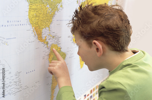 Boy (8-9) looking at world map, close-up