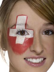 Junge Frau mit Schweizer Flagge auf Gesicht gemalt