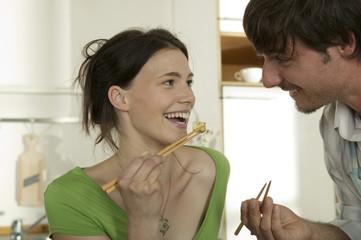 Junges Paar Essen mit Stäbchen, lächeln
