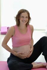 Schwangere Frau sitzt auf Yoga-Matte