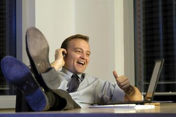 Geschäftsmann telefonierend, Füße auf dem Schreibtisch