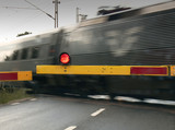 A fast train crossing a road at a railway junction