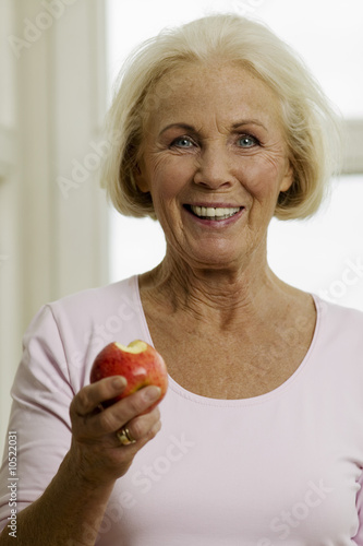 Senior woman eating apple, smiling, close-up, portrait