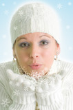 dreamy picture of attractive young girl blowing into snowflakes poster