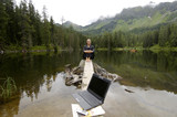 Businesswoman sitting at lake, laptop in foreground