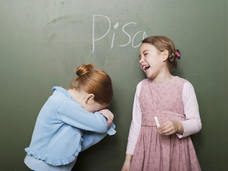 Mädchen stehen vor der Tafel, lachen