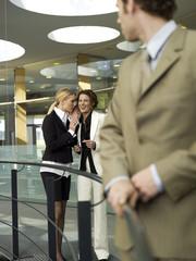 Zwei Geschäftsfrauen Blick auf Mann, Flüstern,
