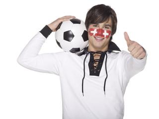 Junger Mann mit schweizer Flagge auf Gesicht gemalt, trägt Fußball auf den Schultern