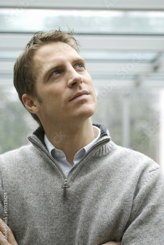 Man looking upwards arms folded