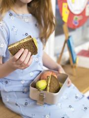 Mädchen halten Lunchpaket, close-up Brotzeit