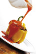 Pouring tomato sauce on bell pepper filled with minced meat, tilt view