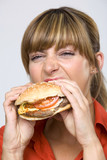 Young woman eating hamburger