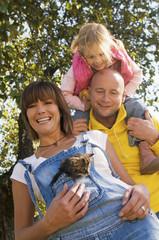 Vater trägt Mädchen auf den Schultern, Frau mit Kätzchen