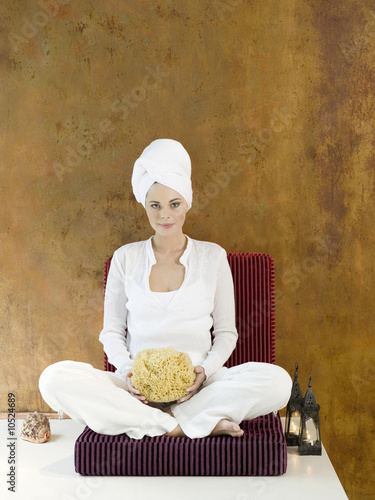 Woman sitting with sponge, smiling