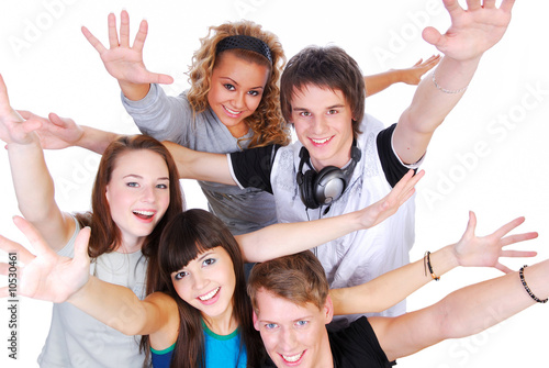 Group of joyful young people with the hands stretched upwards