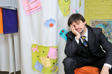 Sleeping well-dressed man waiting in clothes shop