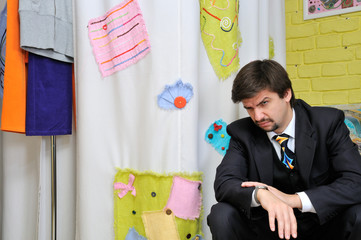 Displeased man sitting and waiting in clothes shop
