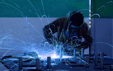 welding worker with sparks arcing